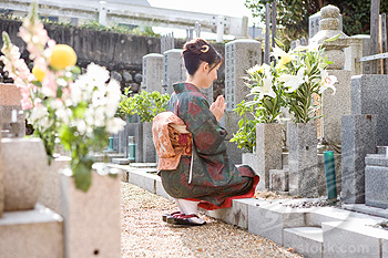 Japan, Kyoto, woman in kimono praying in cemetery